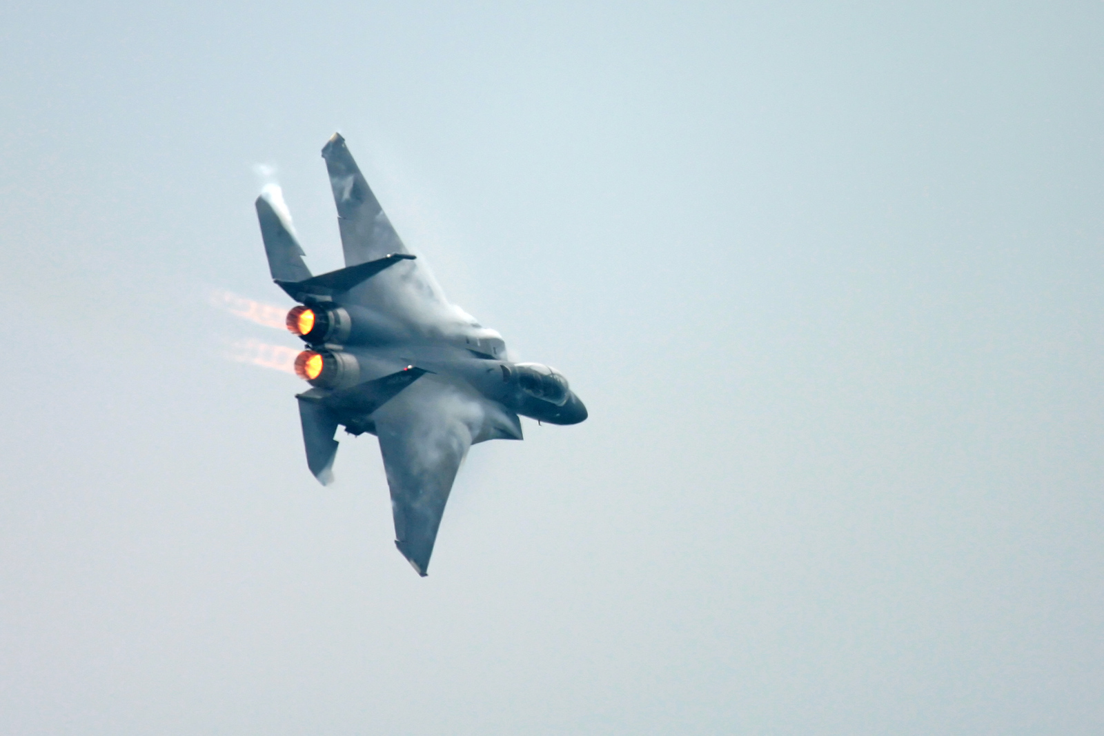 A F15 Eagle fighter jet flying with the afterburners lit up